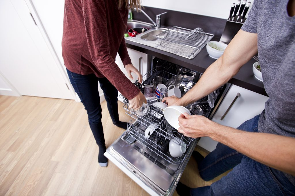 Caucasian couple loading dishwasher together in kitchen